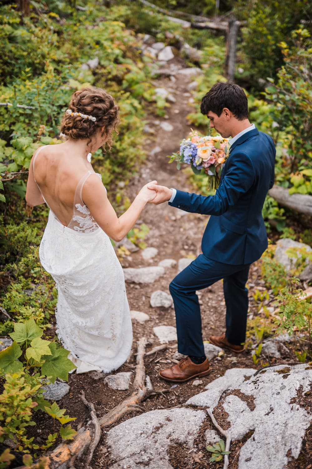 Wedding couple hikes in their wedding attire in Nelson, British Columbia