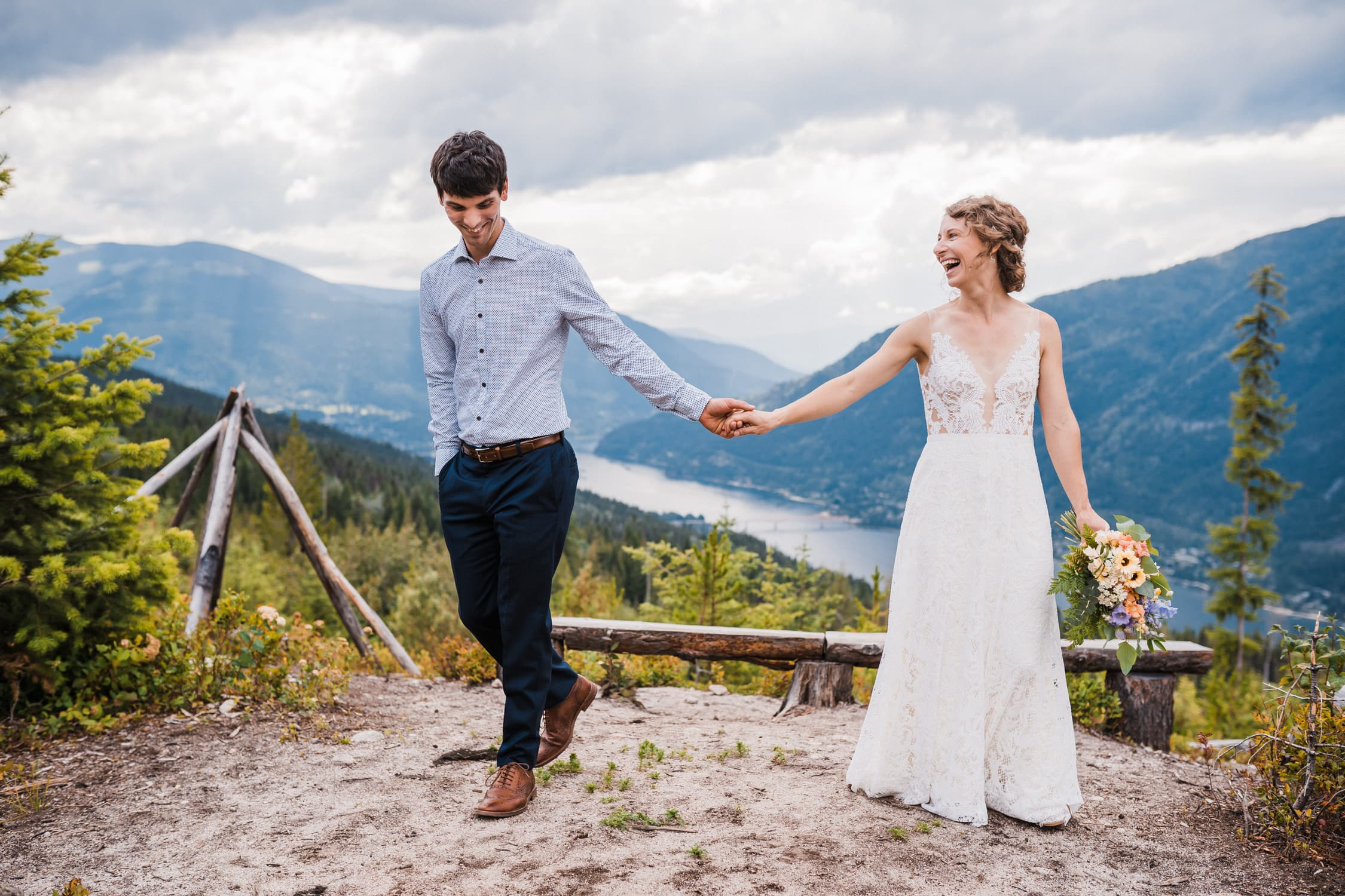 Wedding couple laughs on the top of a mountain in Nelson, BC