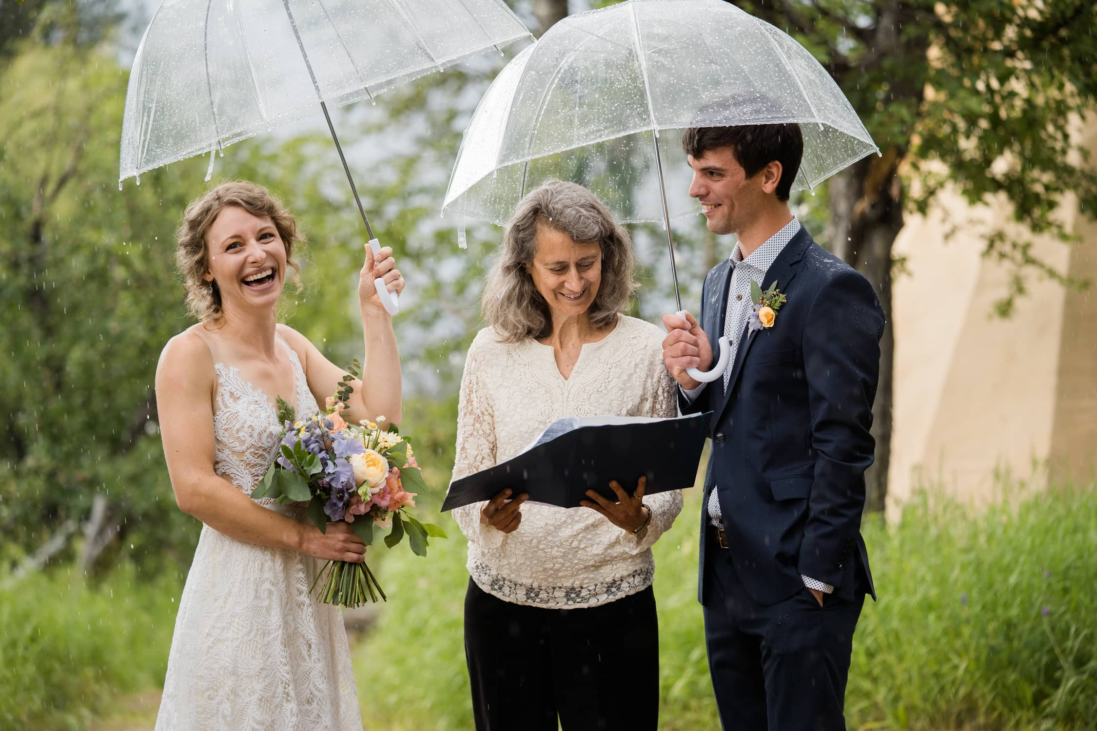 Newlyweds smile as the rain comes down during their ceremony in Nelson, British Columbia