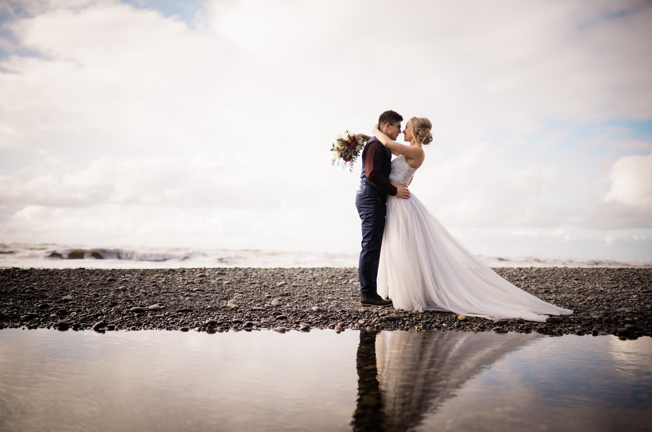 Bride and Groom look into each other's eyes oceanside in Tofino, BC