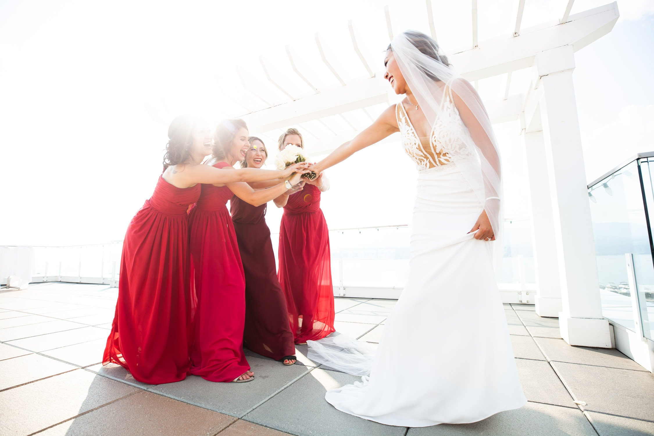 A bride playfully hands her bridesmaids, dressed in full length red dresses, her bouquet with a big smile