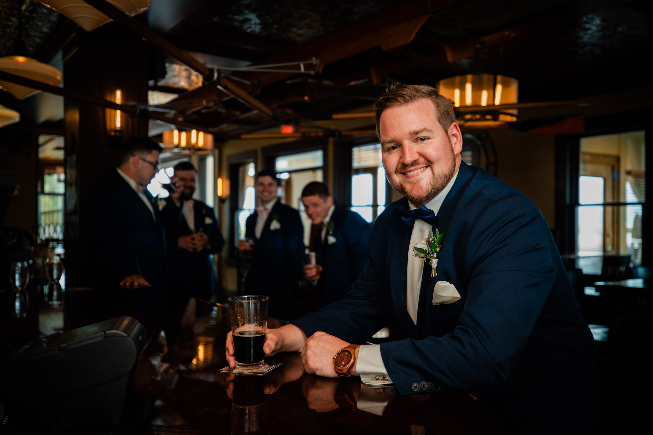 A grooms smiles at the camera while holding a drink in a bar in Kelowna, BC