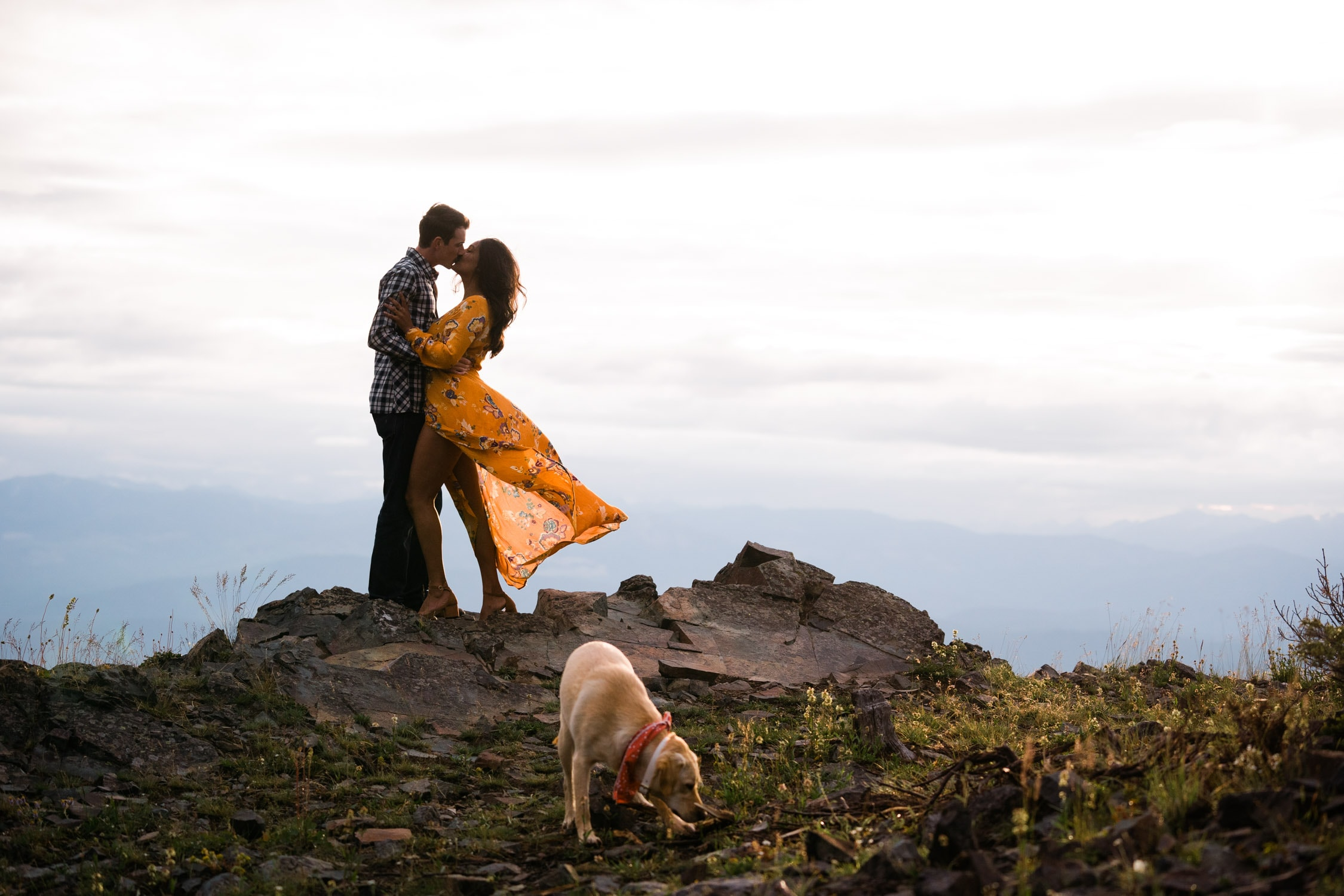 Couple kisses with their dog playing in the foreground while standing on top of a mountain