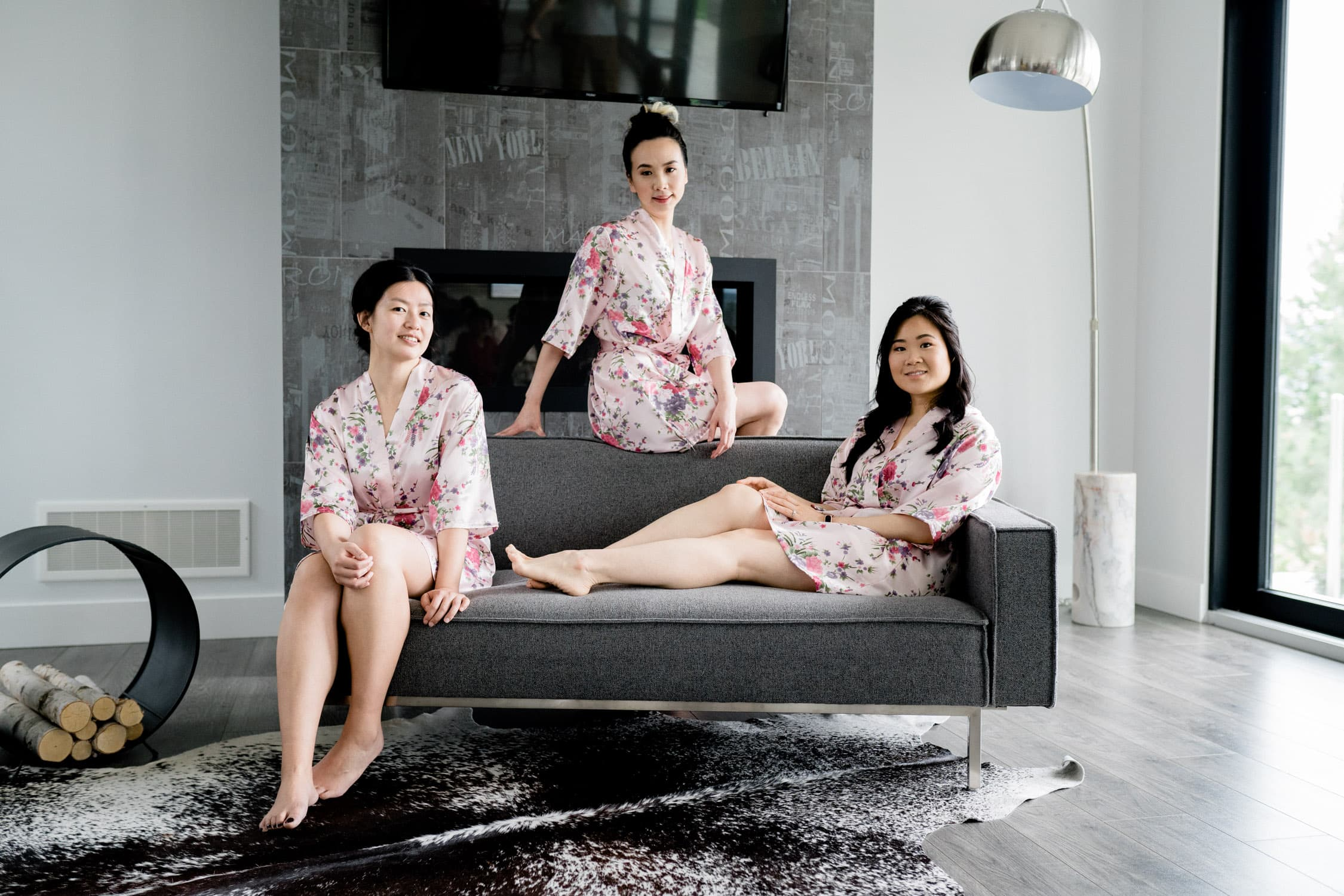 Three Asian bridesmaids lounge on a grey couch in their pink floral dressing robes in a modern AirBnB in Fernie, British Columbia