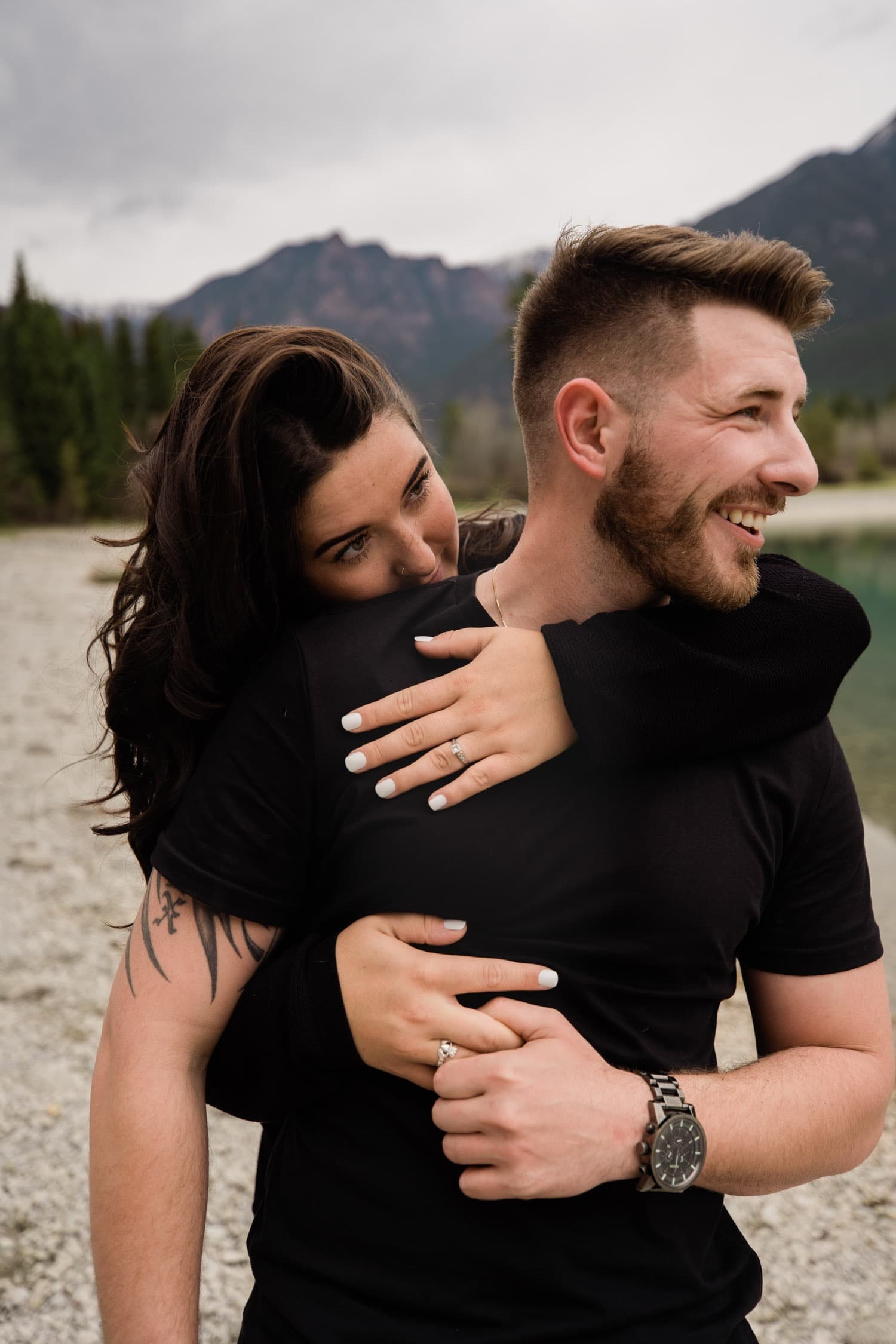 A woman wraps her arms around her partner from behind him. She nuzzles  into his neck as they enjoy the beautiful mountains around them during their adventurous mountain engagement session in Kimberley, BC with photographer Tara Hill Studios