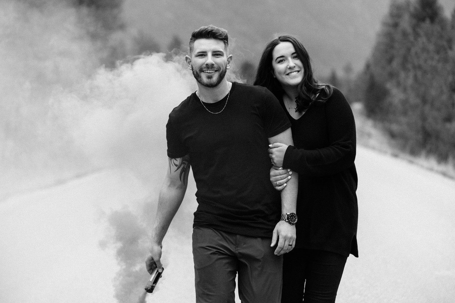 Couple playfully skips towards the camera as they play with smoke bombs during their adventurous mountain engagement session with their photographer Tara Hill Studios