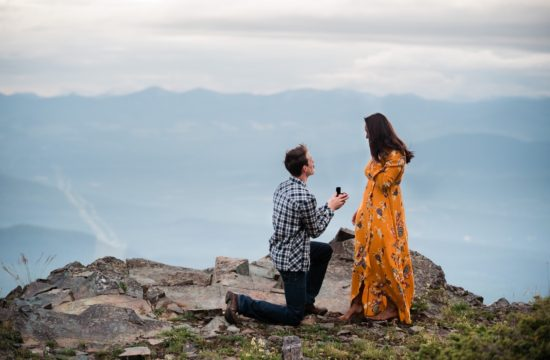 Man down on one knee proposing to his girlfriend in a beautiful flowing yellow dress on top of a mountain in Cranbrook, British Columbia