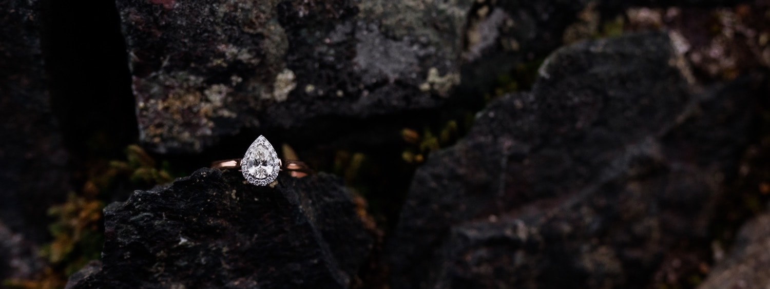 Macro shot of a beautiful pear shaped engagement ring with a dainty halo around the pear stone in rose gold.