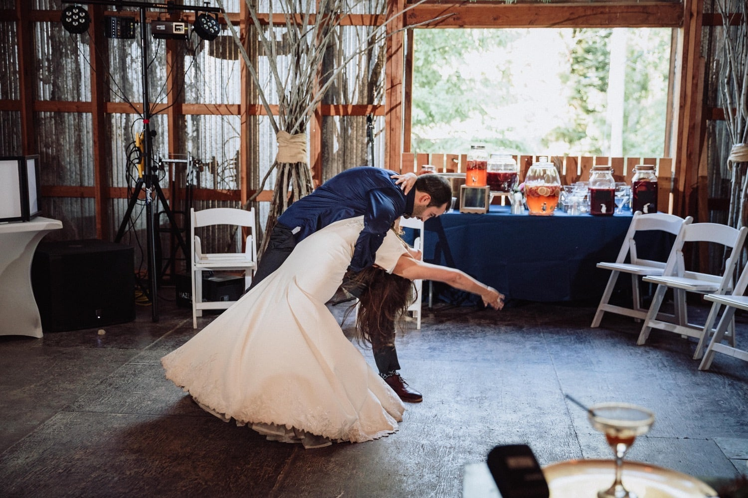 Groom dips his bride at the end of their surprise first dance at their wedding