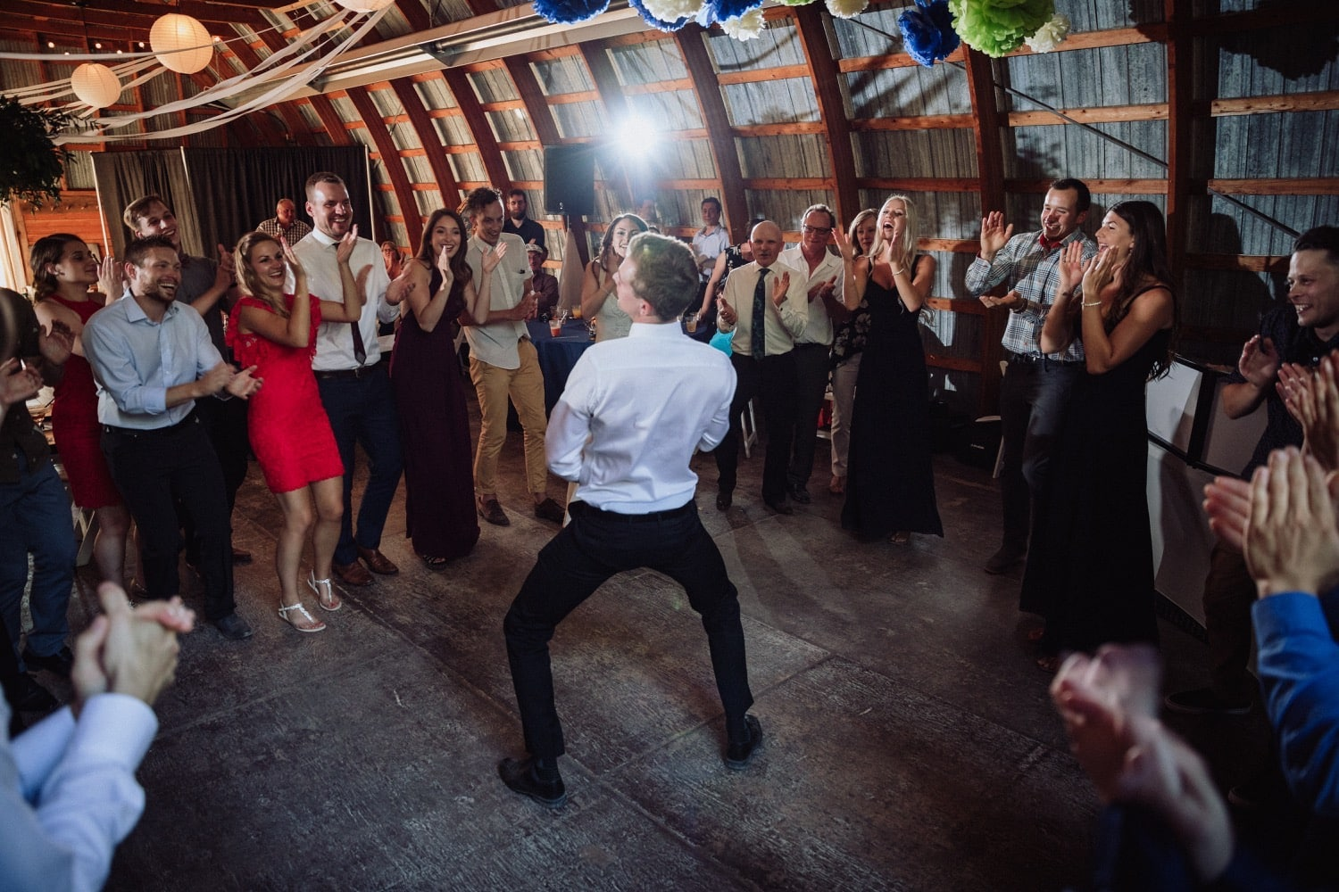 A dance circle has formed at a wedding with one man entertaining everyone in the middle