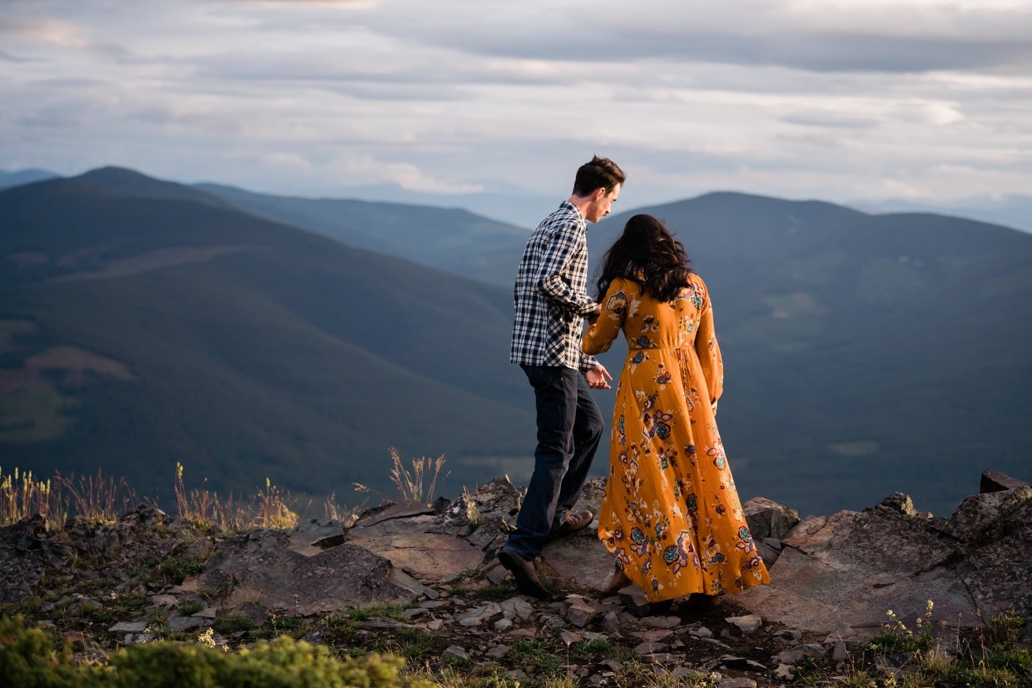 A man in jeans and a plaid button up shirt helps his girlfriend in a yellow flowing dress navigate the rocks on top of a mountain in the East Kootenays