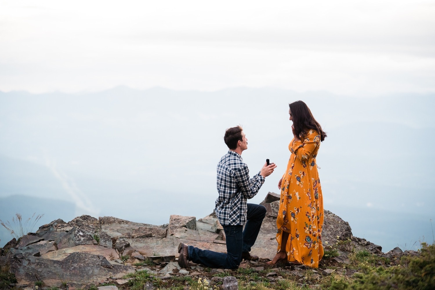 A man in jeans and a blue plaid shirt is down on one knee asking his girlfriend to marry him during their adventurous photography session in Cranbrook, BC
