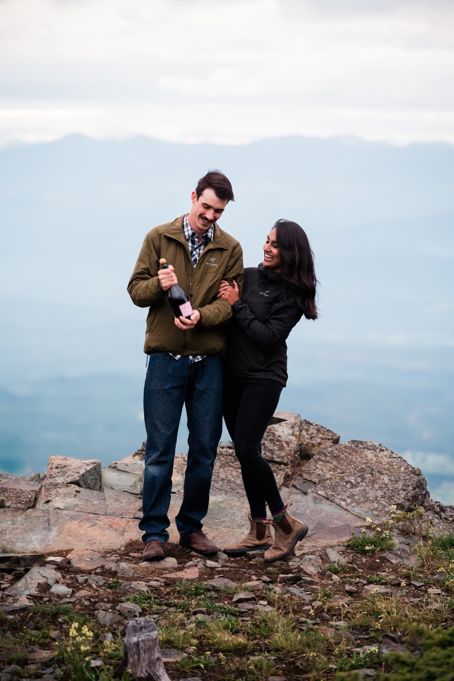 A couple in matching Arcteryx jackets prepare to pop a bottle of champagne on top of a mountain in the East Kootenays with adventure photographer Tara Hill Studios