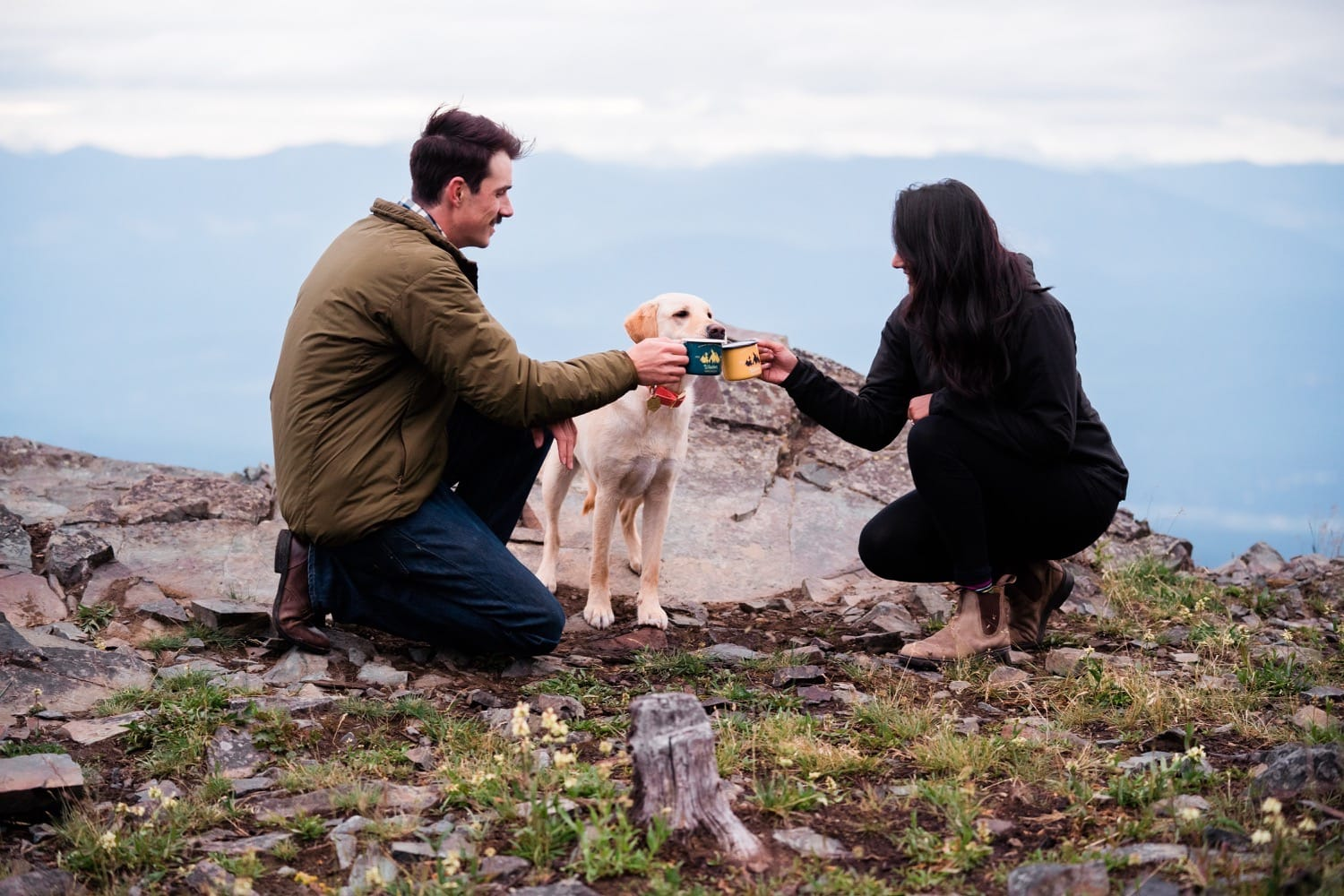 An adventurous couple in hiking clothes cheers each other with camping mugs full of champagne as their dog sniffs the mugs.