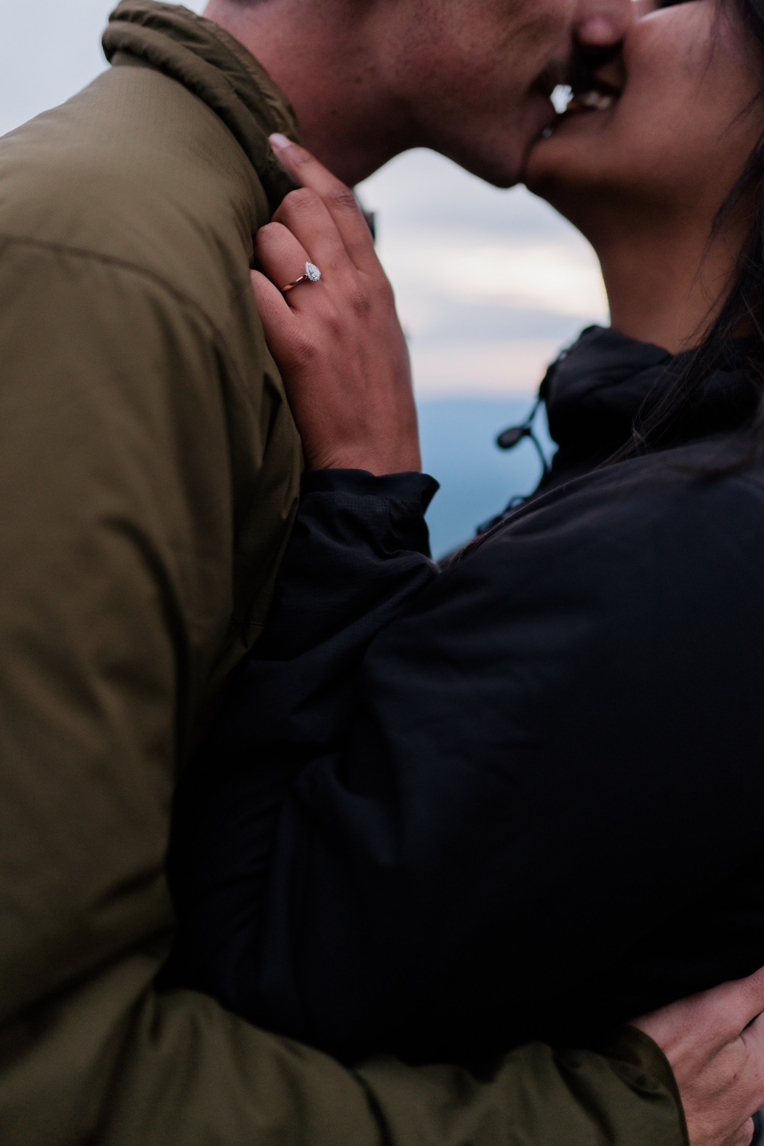 A detail shot of a couple kissing and showing off the engagement ring