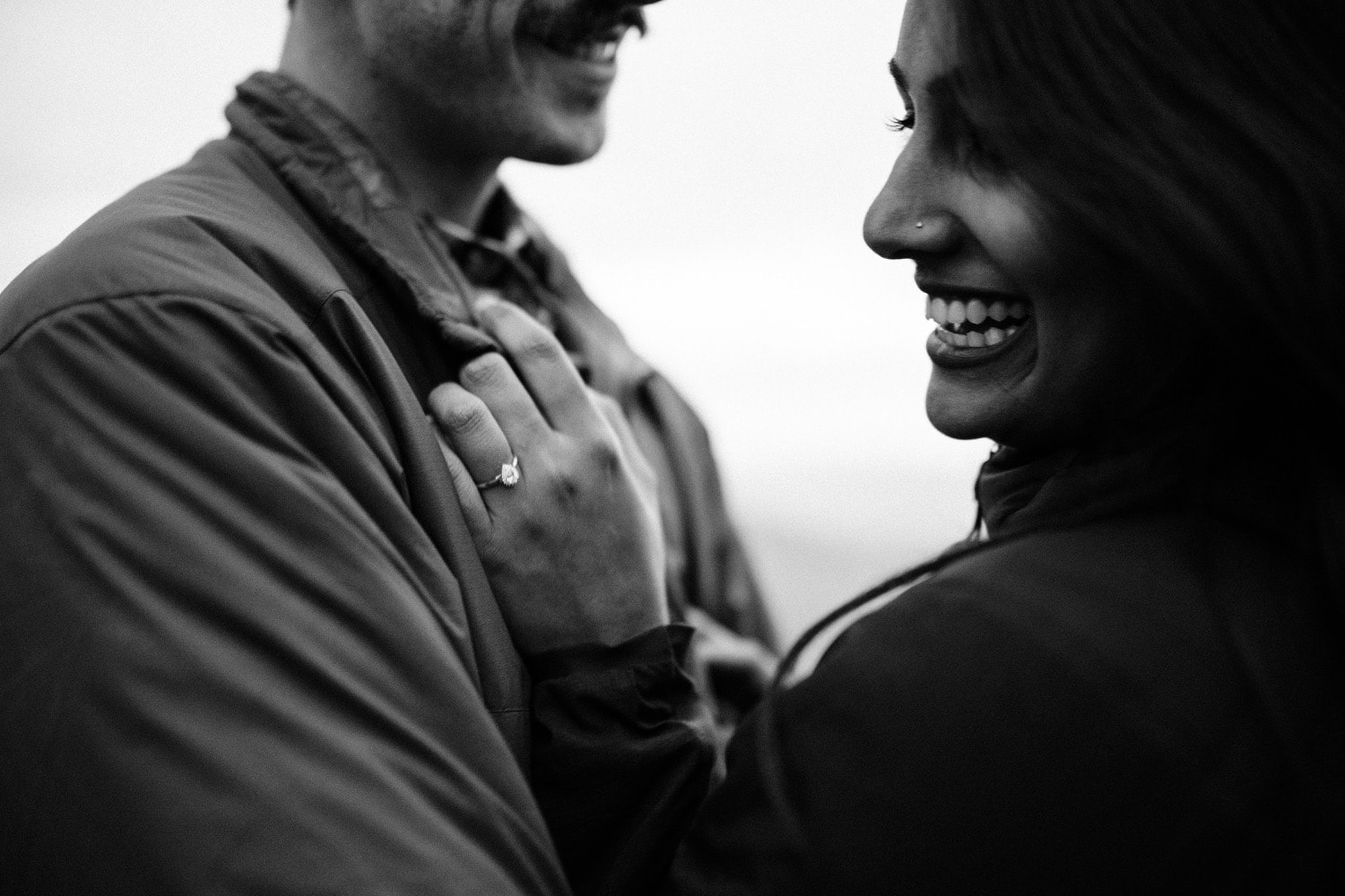 A beautiful Indian woman smiles from ear to ear after her boyfriend proposed to her on top of a mountain during their adventurous couples photography session with Tara Hill Studios