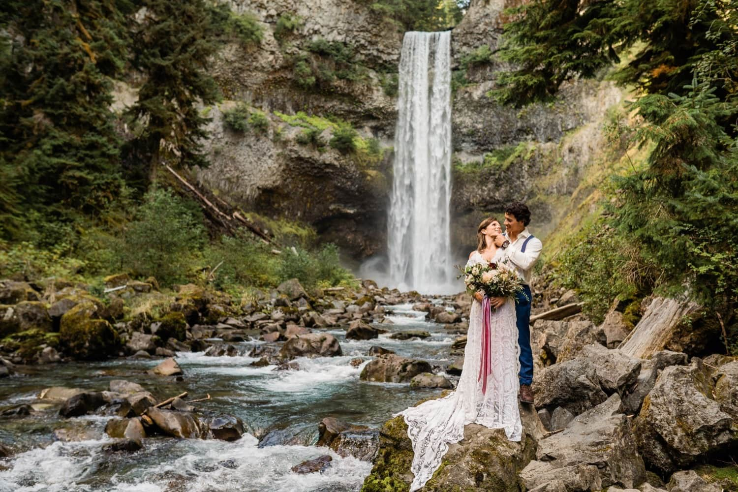 Elopement bride and groom stand at the base of a towering waterfall in Whistler, British Columbia