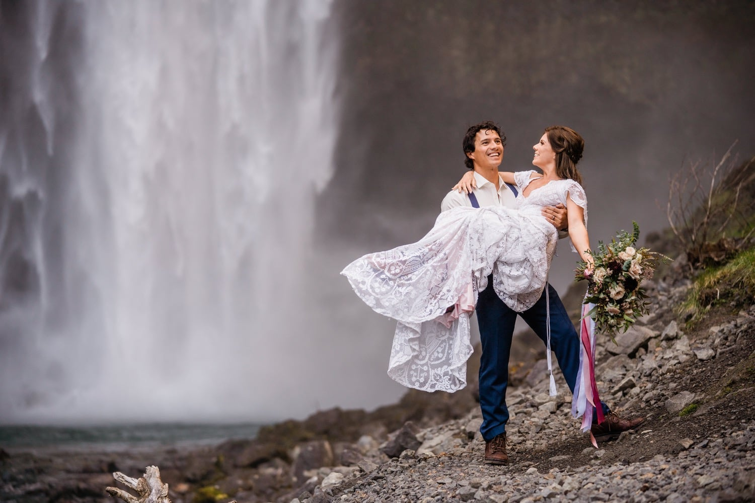 A groom holds his bride and they both smile at the base of a waterfall