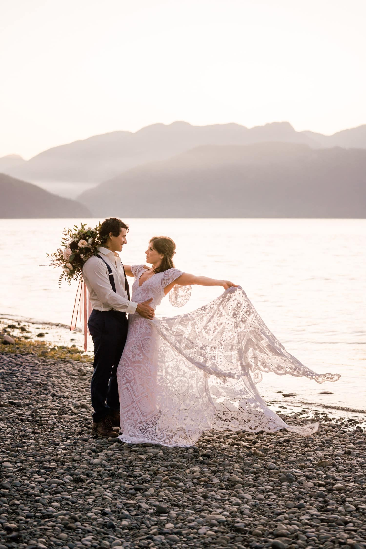 Bride shows off her wedding dress as the sun sets on the coast of British Columbia