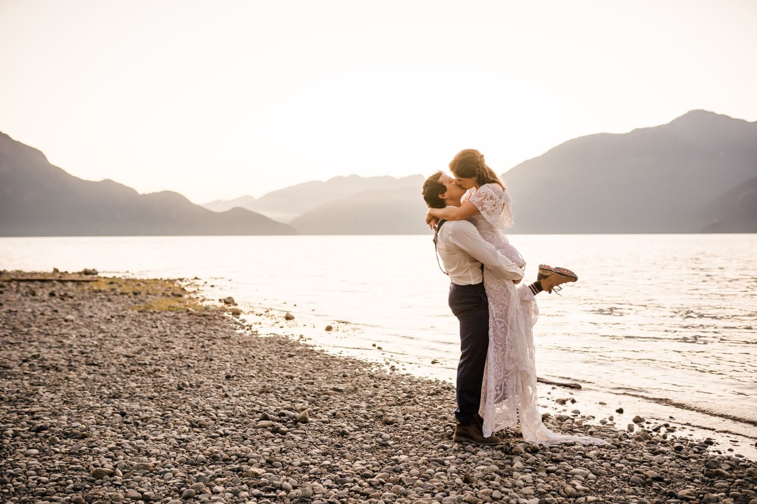 Golden light surrounds a bride and groom as her picks her up and kisses her beside the ocean